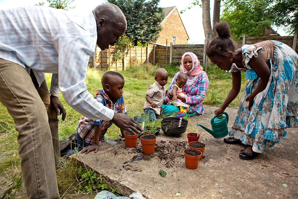 A photo of a family watering plants in a garden